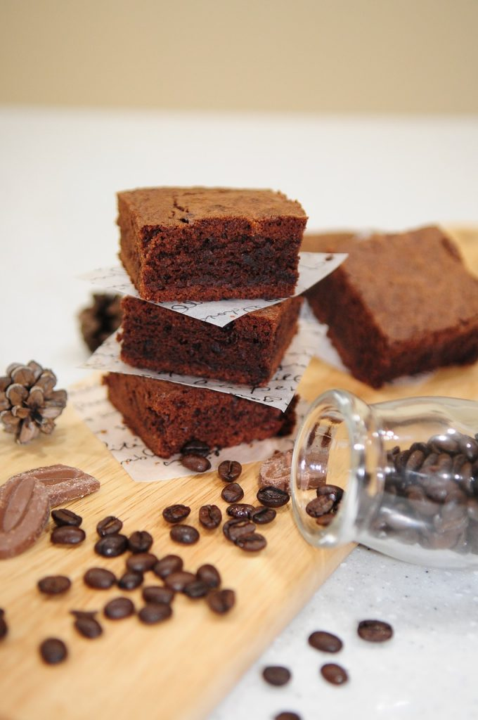 Coffee flour brownies on table with coffe around them